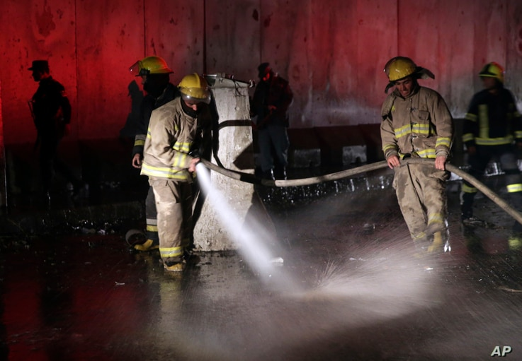 Afghan firefighters wash the site of a twin bombing in Kabul, Afghanistan, Jan. 10, 2017.