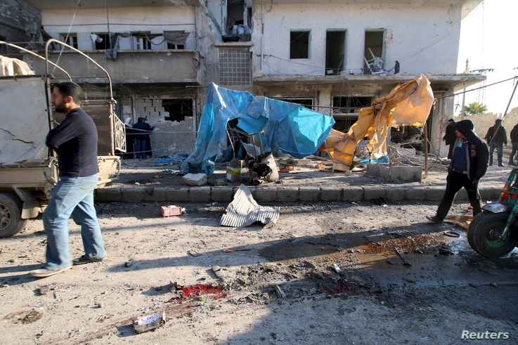 Residents inspect the damage as blood stains are seen on the ground after airstrikes by pro-Syrian government forces in the rebel-held al-Sakhour neighborhood of Aleppo, Syria, Feb. 8, 2016.