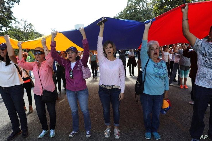 Members of the opposition hold up a Venezuelan flag and sing their national anthem before handing out explainers to soldiers and police about an amnesty law, near Ft. Tiuna military base in Caracas, Venezuela, Jan. 27, 2019.