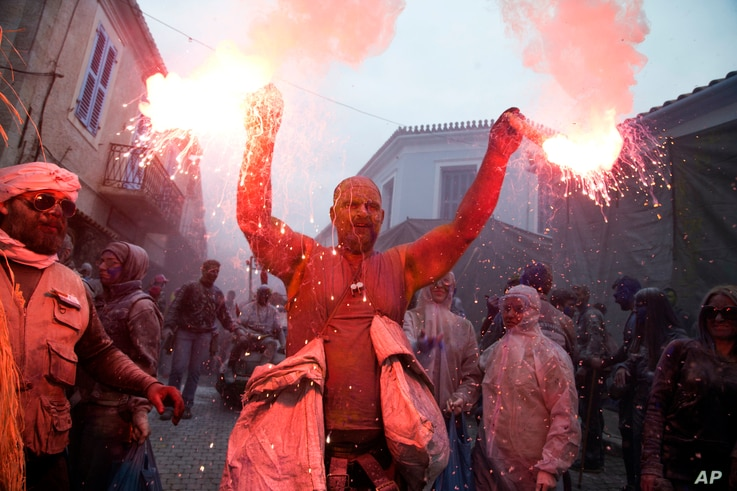 A reveler lights up the Clean Monday festivities with two flares in Galaxidi, Greece, Fev. 19, 2018.