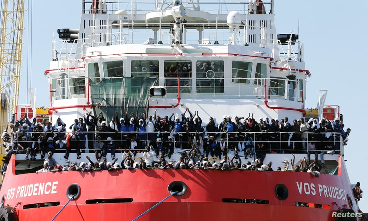 """FILE - Migrants wait to disembark from """"Vos Prudence"""" offshore tug supply ship as they arrive at the harbor in Naples, Italy, May 28, 2017."""