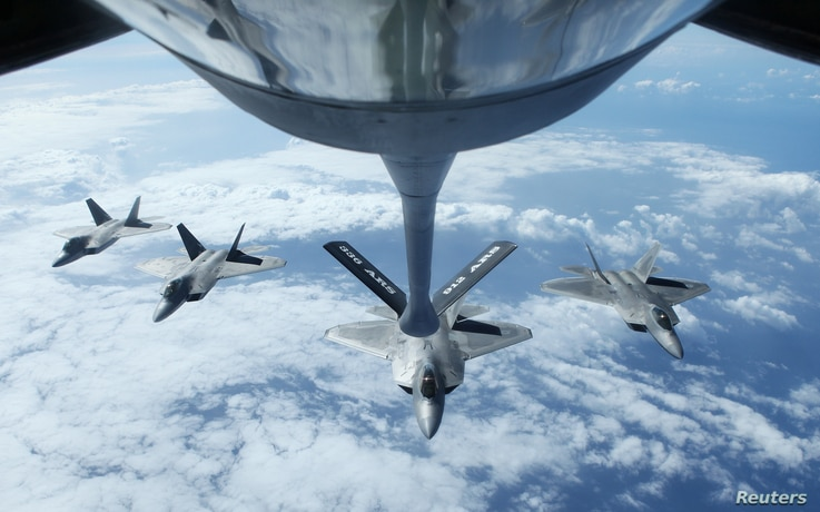 Four F22 Raptors fly in formation after a mid-air refueling exercise with a KC-135R Stratotanker as they participate in the multi-national military exercise RIMPAC in Honolulu, Hawaii, July 26, 2016.