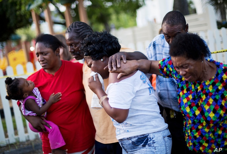 Gary and Aurelia Washington, center left and right, the son and granddaughter of Ethel Lance who died in Wednesday's shooting, leave a sidewalk memorial in front of Emanuel AME Church comforted by fellow family members, June 18, 2015, in Charleston,