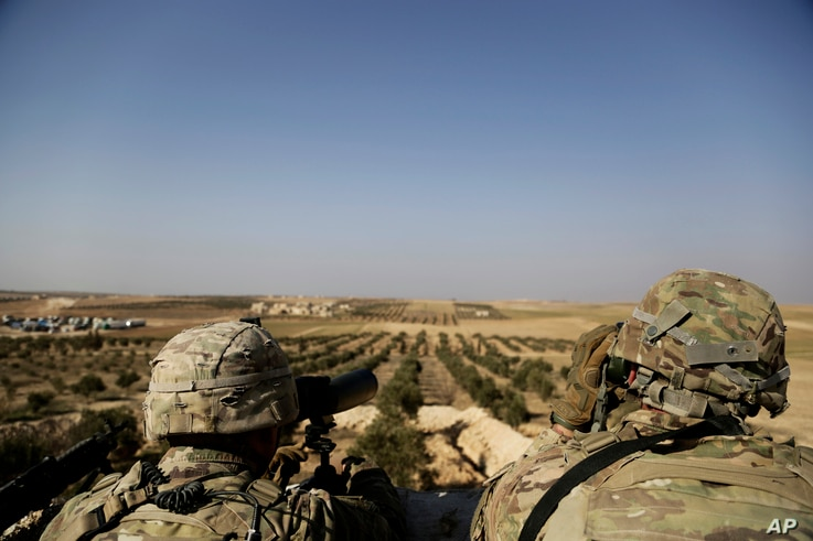 American troops look out toward the border with Turkey from a small outpost near the town of Manbij, northern Syria, Feb. 7, 2018.