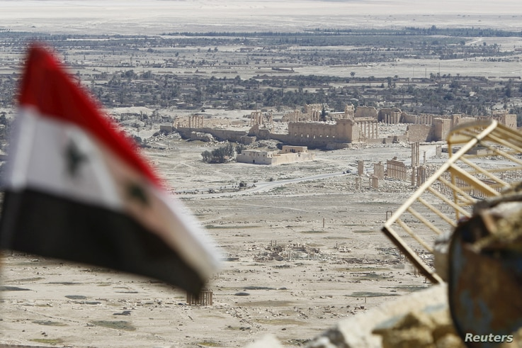FILE - A Syrian national flag flutters as the ruins of the historic city of Palmyra are seen in the background, in Homs Governorate, Syria, April 1, 2016.