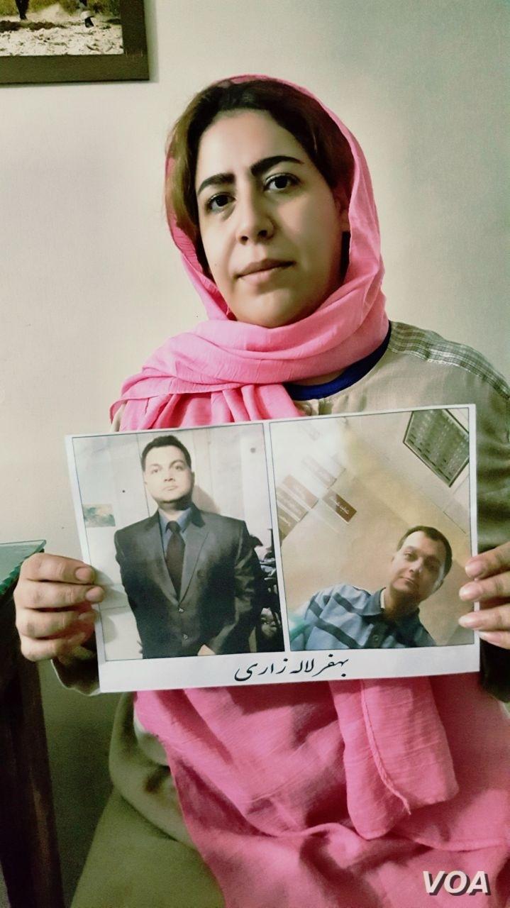 Tehran resident Rezvan Beigi holds photos of her jailed husband Behfar Lalezari, whose life she said is in danger because he has been denied medical treatment in a hospital for serious health problems.