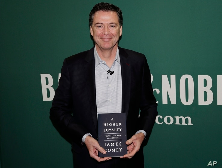 Former FBI director James Comey poses for photographs at a Barnes & Noble book store before speaking, April 18, 2018, in New York.