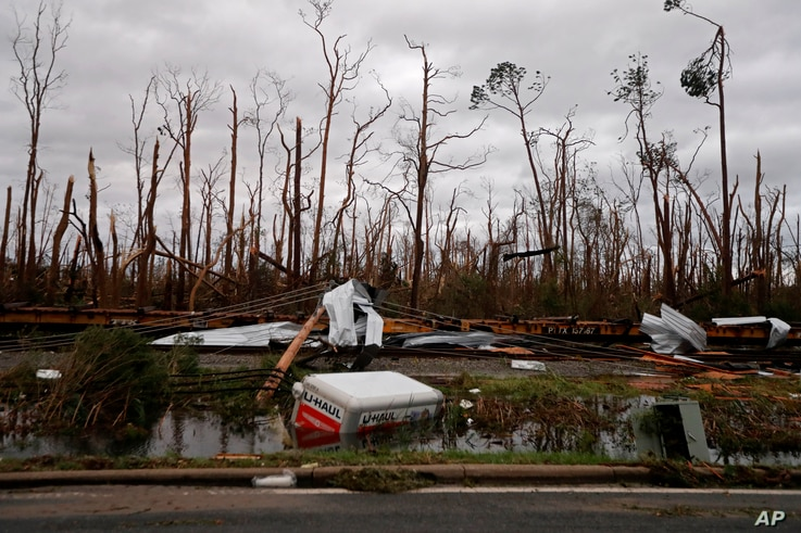 Shredded trees, derailed train cars and a sunken trailer are seen in the aftermath of Hurricane Michael in Panama City, Fla., Oct. 10, 2018.