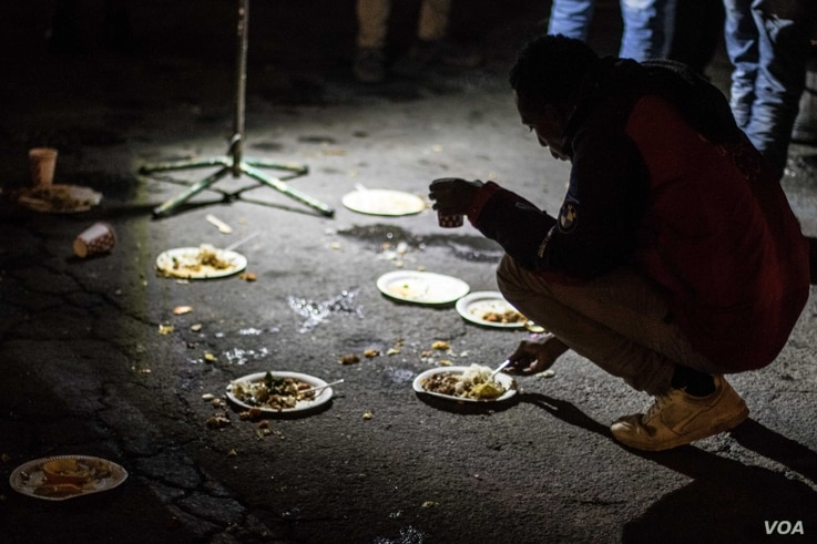 Migrants and refugees have dinner near the underpass in Ventimiglia, Italy. Many wait until nightfall to attempt their crossing in France.