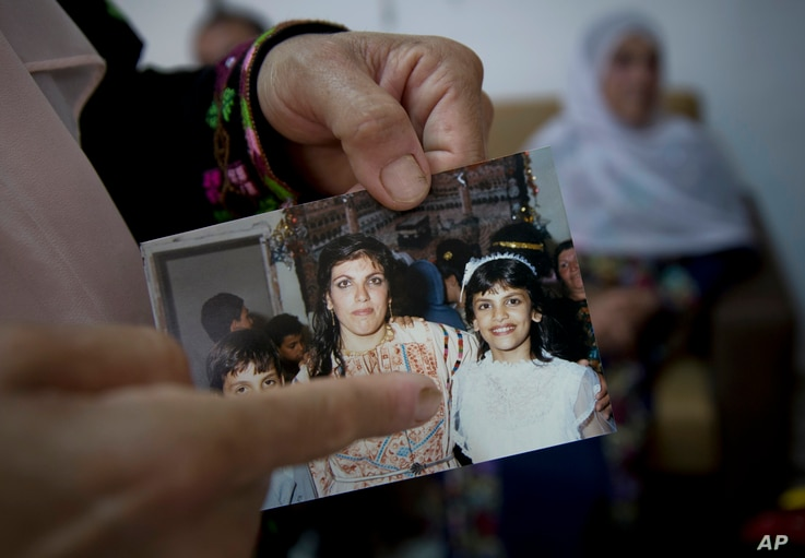 In this Aug. 8, 2018 photo, Fadwa Tlaib, an aunt of Rashida Tlaib points to a young Rashida Tliab in a 1987 picture with her mother Fatima and brother Nader, at the family house, in the West Bank village of Beit Ur al-Foqa.