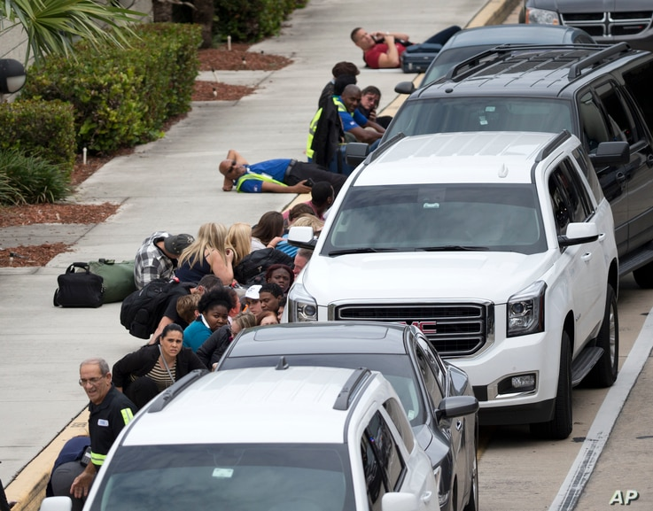 People take cover outside Fort Lauderdale-Hollywood International Airport in Fort Lauderdale, Fla., after a shooter opened fire inside a terminal, Jan. 6, 2017.