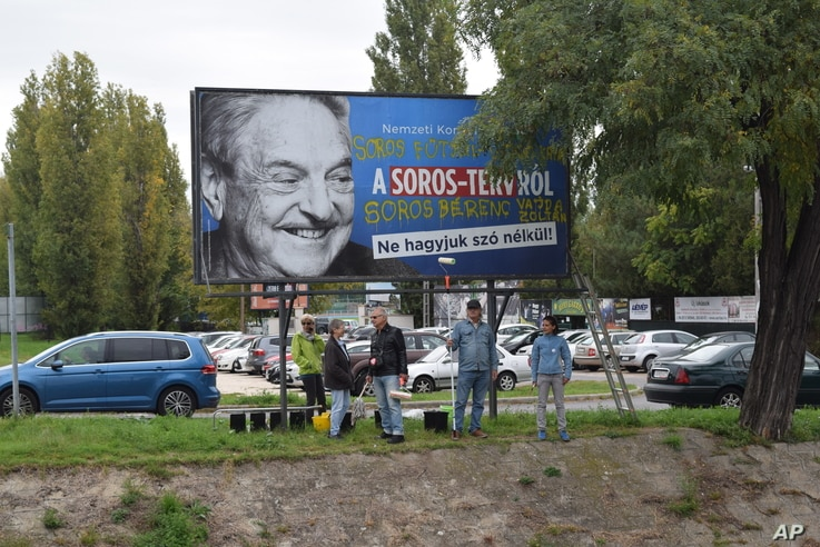 FILE - Activists from the Egyutt (Together) opposition party stand in front of billboards of the government's campaign against George Soros and his support for migration in Budapest, Oct. 5, 2017.