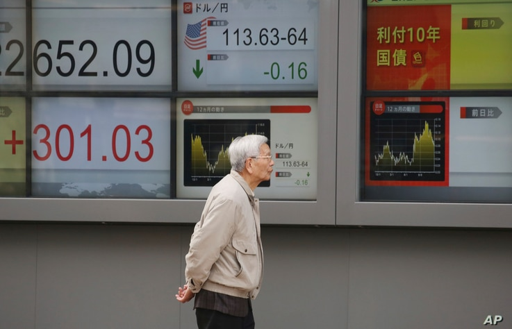 A man walks by an electronic stock board of a securities firm in Tokyo, Monday, Dec. 3, 2018. Shares are advancing in Asia following the meeting between Presidents Donald Trump and Xi Jinping.