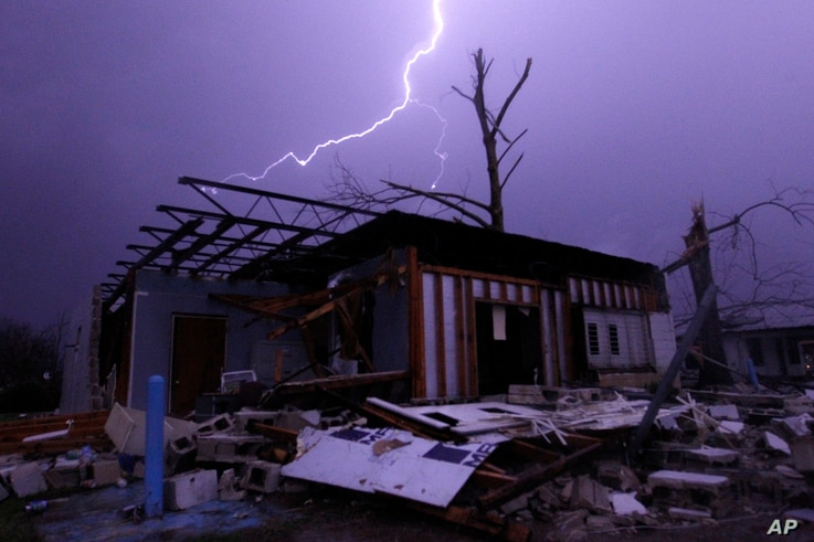 Lightning illuminates a house after a tornado touched down in Jefferson County, Ala., damaging several houses in Birmingham, Dec. 25, 2015.