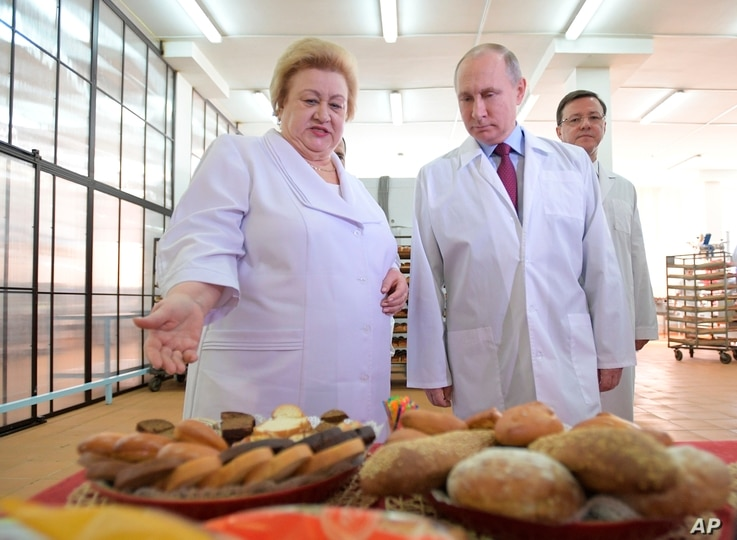 Russian President Vladimir Putin, right, looks at bread and confectionery during his visit to the Samara bakery and confectionery factory on the eve of International Women's Day in Samara, Russia, March 7, 2018.