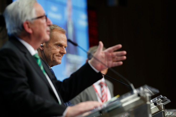 European Commission President Jean-Claude Juncker, left, and European Council President Donald Tusk, center, participate in a media conference at an EU summit in Brussels, Dec. 14, 2018.