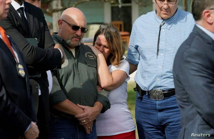 Pastor Frank Pomeroy, with his wife Sherri, listens at a news conference outside the site of the shooting at his church, the First Baptist Church of Sutherland, Texas, Nov. 6, 2017.