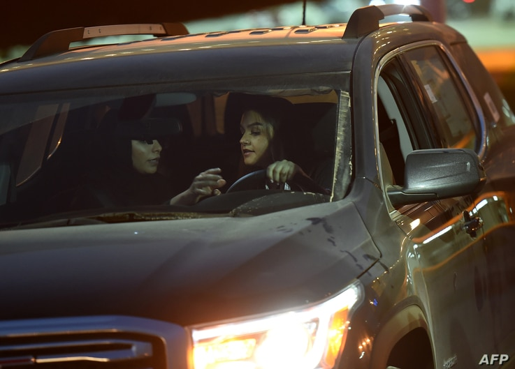 FILE - Saudi women test-drive a car during an automotive exhibition for women in the capital, Riyadh, May 13, 2018.