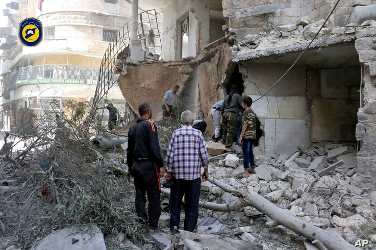 In this photo provided by the Syrian Civil Defense 'White Helmets,' rescue workers work the site of airstrikes in al-Mashhad neighborhood in the rebel-held part of eastern Aleppo, Sept. 21, 2016.