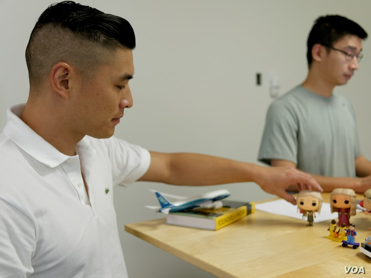 Listia co-founder James Fong, foreground, displays some of the collectibles traded on the website. (M. O'Sullivan/VOA)