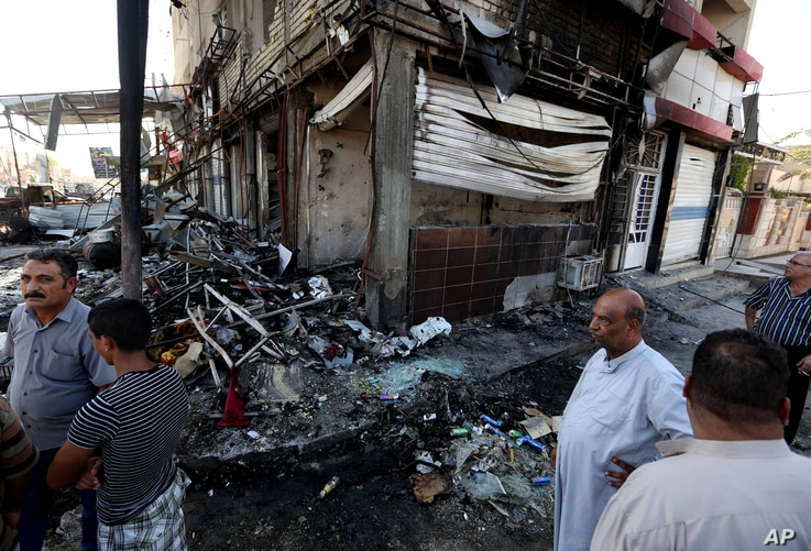 Civilians inspect damages the morning after a string of car bombs tore through busy shopping streets in several neighborhoods in Baghdad, Iraq, Aug. 7, 2014.