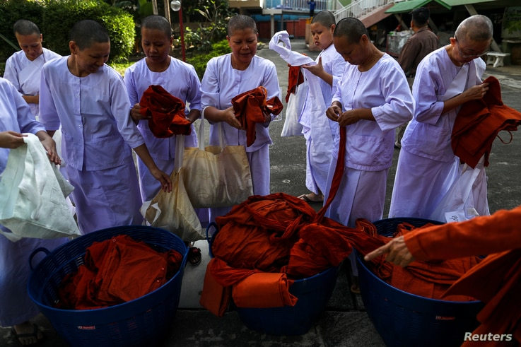 Thai women devotees wearing white robes return saffron robes after ending their novice monkhood at the Songdhammakalyani monastery, Nakhon Pathom province, Thailand, Dec. 14, 2018. Officially, only men can become monks and novices in Thailand.