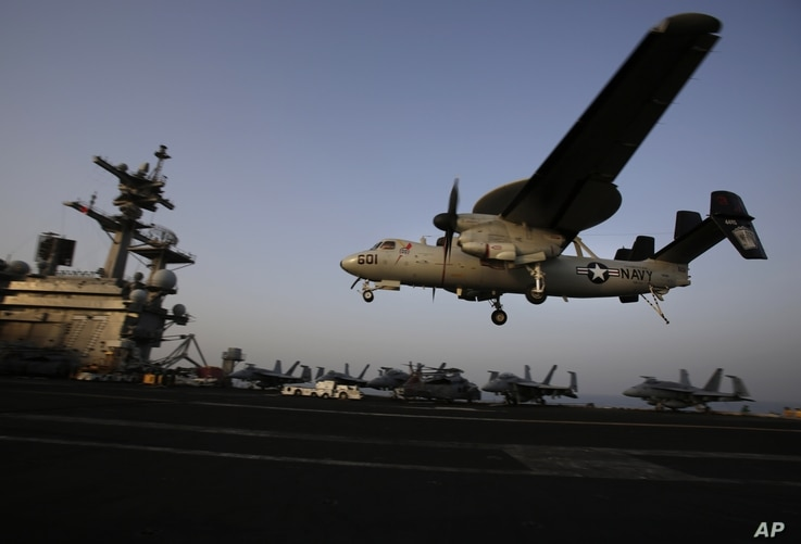 FILE - In this Aug. 10, 2014, file photo, an aircraft lands after missions targeting the Islamic State group in Iraq from the deck of the U.S. Navy aircraft carrier USS George H.W. Bush in the Persian Gulf.