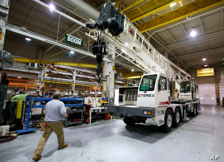 FILE - A worker walks past a crane on the assembly line at the Terex Corporation plant in Waverly, Iowa.