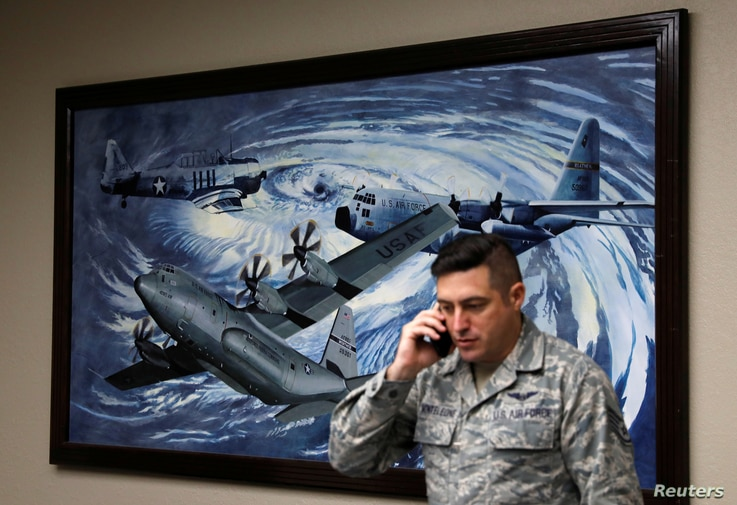 """FILE - U.S. Air Force reserve citizen airman Staff Sgt. Nicholas Monteleone speaks on the phone beside a painting of planes flying through a hurricane at Keesler Air Force Base, home of the 53rd Weather Reconnaissance Squadron know as """"Hurricane Hunt..."""