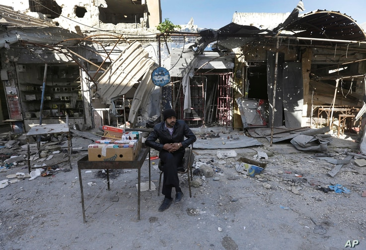 A street vendor who sells cigarette boxes sits in front of shops which were damaged by shelling, Maarat al-Nuaman, Idlib province, Syria, Feb. 26, 2013.