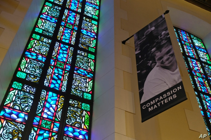In this  Feb. 12, 2019 photo, a banner hangs by a stained glass window in the sanctuary at Glide Memorial United Methodist Church in San Francisco.