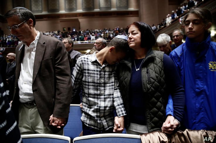 People mourn in Soldiers & Sailors Memorial Hall & Museum during a community gathering held in the aftermath of Saturday's deadly shooting at the Tree of Life Synagogue in Pittsburgh, Sunday, Oct. 28, 2018.