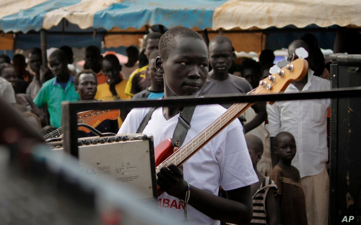 """In this photo taken Saturday, Nov. 5, 2016, a guitarist at an Ana Taban, or """"I am tired"""" artists movement roadshow, plays in front of an audience in Juba, South Sudan. For many in South Sudan, the arts have become a rare haven of peace in a young cou..."""