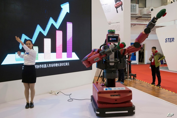 FILE - A woman demonstrates the ability of Baxter, an industrial robot from U.S. company Rethink Robotics, to follow her hand movements during the World Robot Conference in Beijing, Oct. 21, 2016.