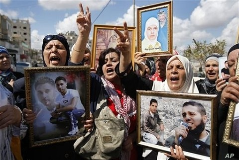 Palestinian women hold portraits of relatives held in Israeli jails during a protest calling for the release of Palestinian prisoners, in the West Bank city of Nablus, Tuesday 6 Oct. 2009
