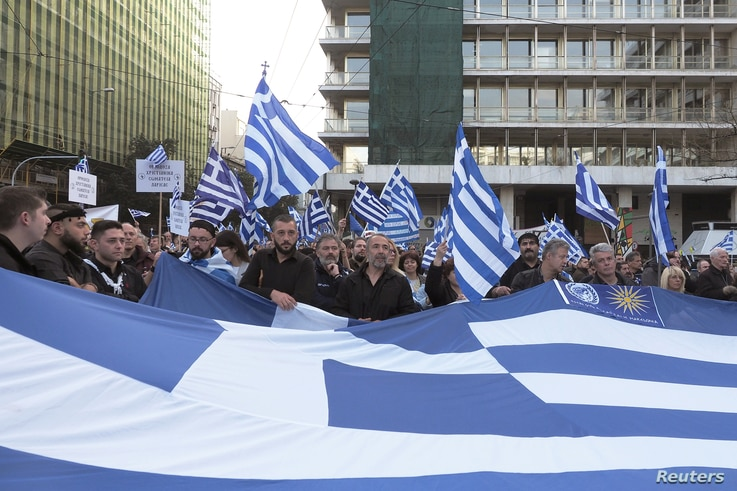"""Protesters hold a Greek flag during a rally against the use of the term """"Macedonia"""" in any settlement to a dispute between Athens and Skopje over the former Yugoslav republic's name, in Athens, Greece, Feb. 4, 2018."""