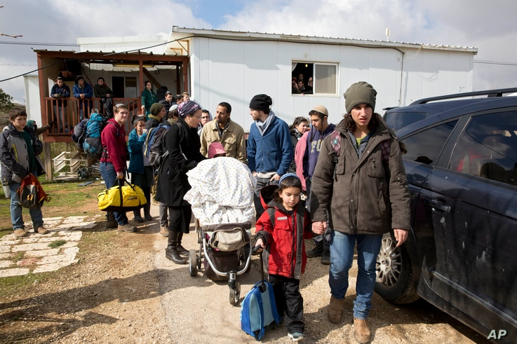 Settler families leave their homes in the West Bank outpost of Amona, Feb. 1, 2017. Israeli forces have begun evacuating the controversial settlement, which is the largest of about 100 unauthorized outposts erected in the West Bank without permission...