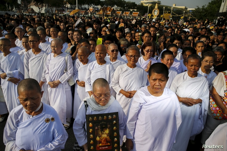 FILE - Nuns and people take part in a procession with the royal carriage containing the remains of Thailand's Supreme Patriarch, Somdet Phra Nyanasamvara Somdet Phra Sangharaja, during his cremation ceremony in Bangkok, Thailand, December 16, 2015.