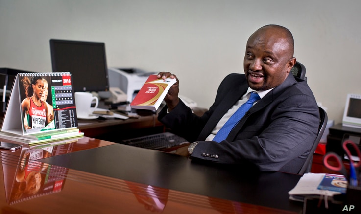 FILE - Athletics Kenya CEO Isaac Mwangi holds up a copy of the IAAF Competition Rules book, to illustrate his denial that Athletics Kenya would have the power to shave time off athletes' bans, in Nairobi, Kenya, Feb. 8, 2016.