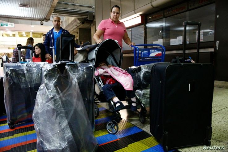 FILE - Natalie Pereira (C) queues to go through migration before her move to the U.S. with her family, after winning the Green Card lottery, at the Maiquetia airport in Caracas, Apr. 8, 2014.