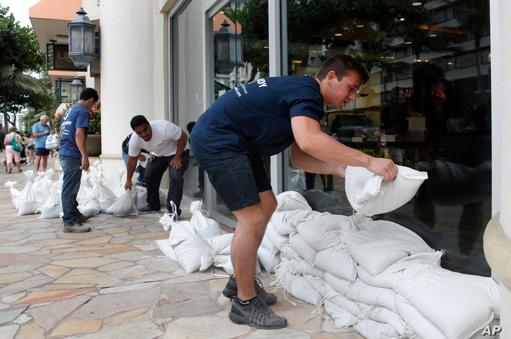 Austin Seawright (R) stacks sandbags in front of a closed store in preparation for Hurricane Lane, Aug. 23, 2018, in Honolulu.