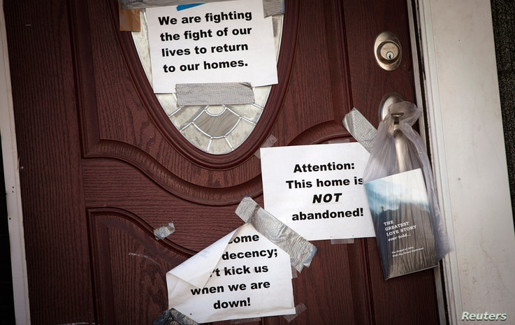 Signs are taped to the front door of a home in the New Dorp Beach area in the Staten Island borough of New York, Sept. 20, 2013.