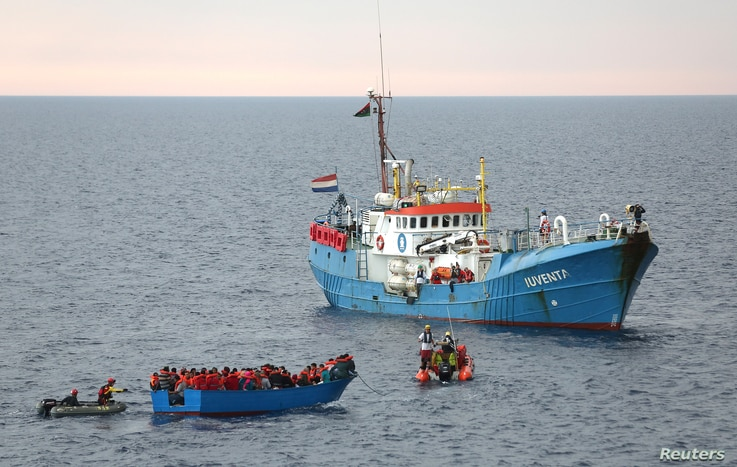 FILE - Migrants on a wooden boat are rescued by crew from the German NGO Jugend Rettet ship Iuventa in the Mediterranean Sea off Libya coast, June 18, 2017.