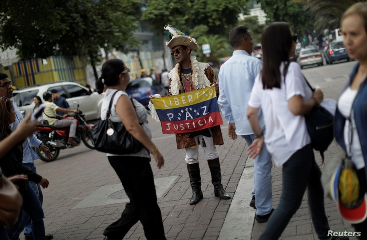 """A man holding a Venezuela flag with the words """"Freedom, peace, justice"""" stands on a street in Caracas, Venezuela, July 21, 2017."""
