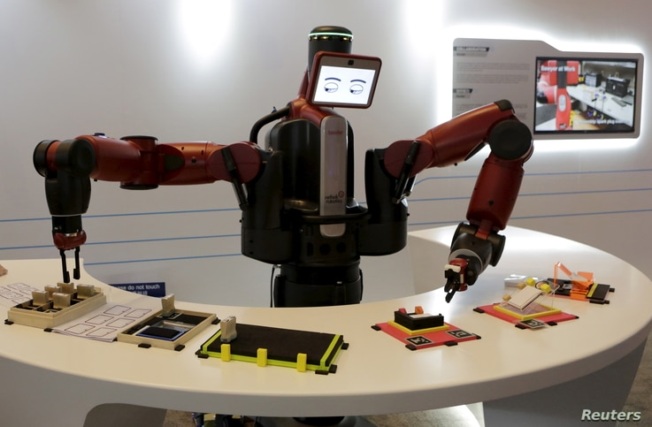 FILE - A Baxter robot of Rethink Robotics picks up a business card as it performs during a display at the World Economic Forum (WEF), in China's port city Dalian, Liaoning province, China onSept. 9, 2015.