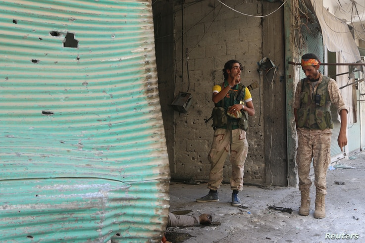 Syria Democratic Forces (SDF) fighters inspect a dead body of what they said was an Islamic State fighter inside a shop in Manbij, in Aleppo Governorate, Syria, August 7, 2016.