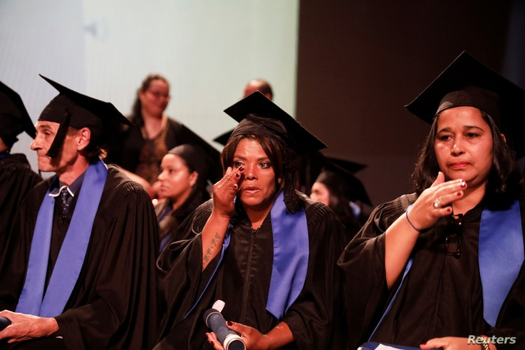Fabiana Silva, a former crack user who now collects recyclable materials, holds her certificate as she wipes a tear at her middle school graduation ceremony at Coracao de Jesus school in downtown Sao Paulo, Brazil, June 29, 2017.