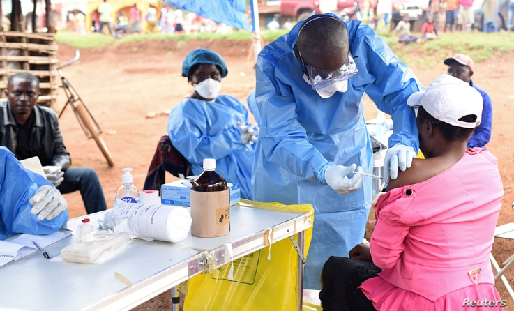 FILE - A Congolese health worker administers Ebola vaccine to a woman who had contact with an Ebola sufferer in the Democratic Republic of Congo, Aug. 18, 2018.