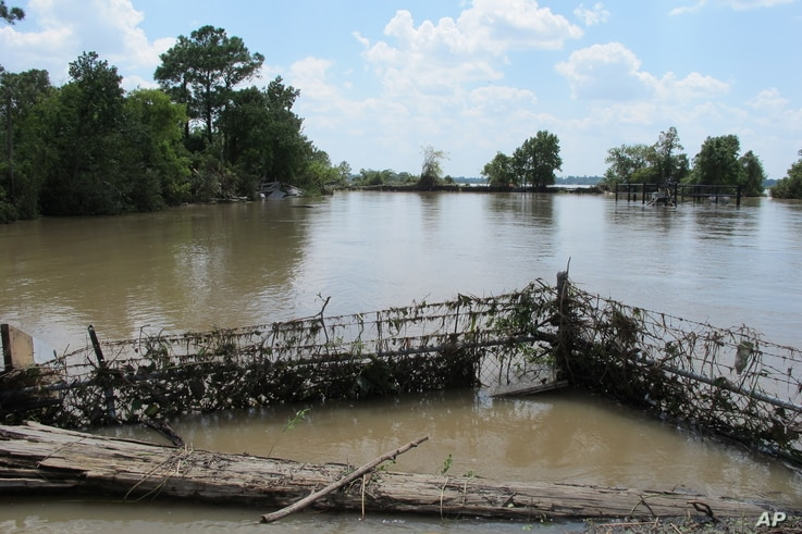 FILE - In this Aug. 31, 2017, photo, a barbed-wire fence encircles the Highlands Acid Pit that was flooded by water from the nearby San Jacinto River as a result from Harvey in Highlands, Texas.  Floodwaters have inundated at least five highly contam...