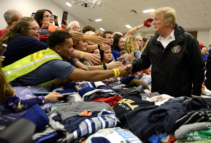U.S. President Donald Trump greets volunteers who have sorted donated clothing at the Providence Baptist Church in Beauregard, Alabama, March 8, 2019.
